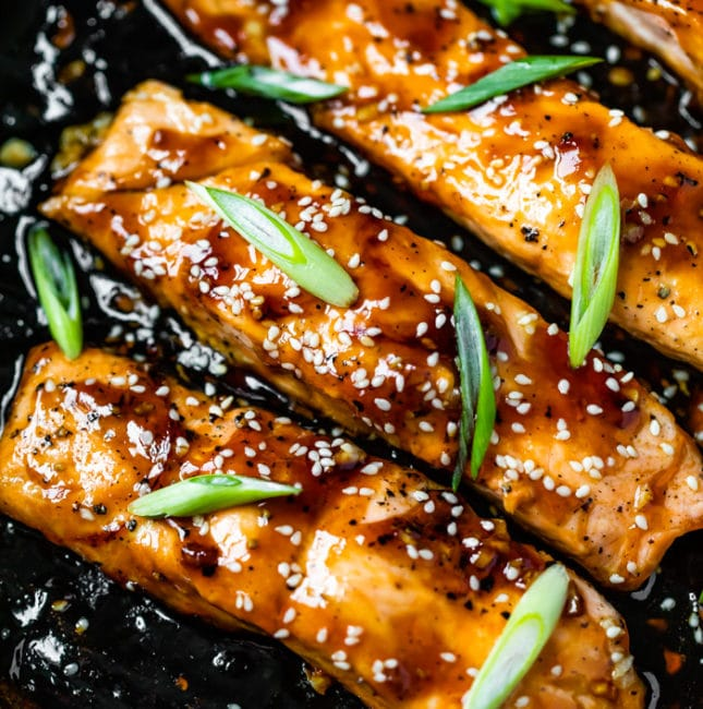 salmon in a skillet with scallions