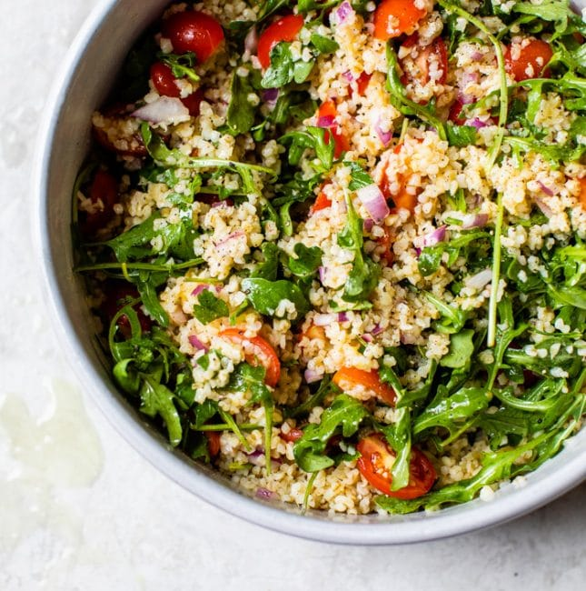 salad in a bowl with grains and tomato