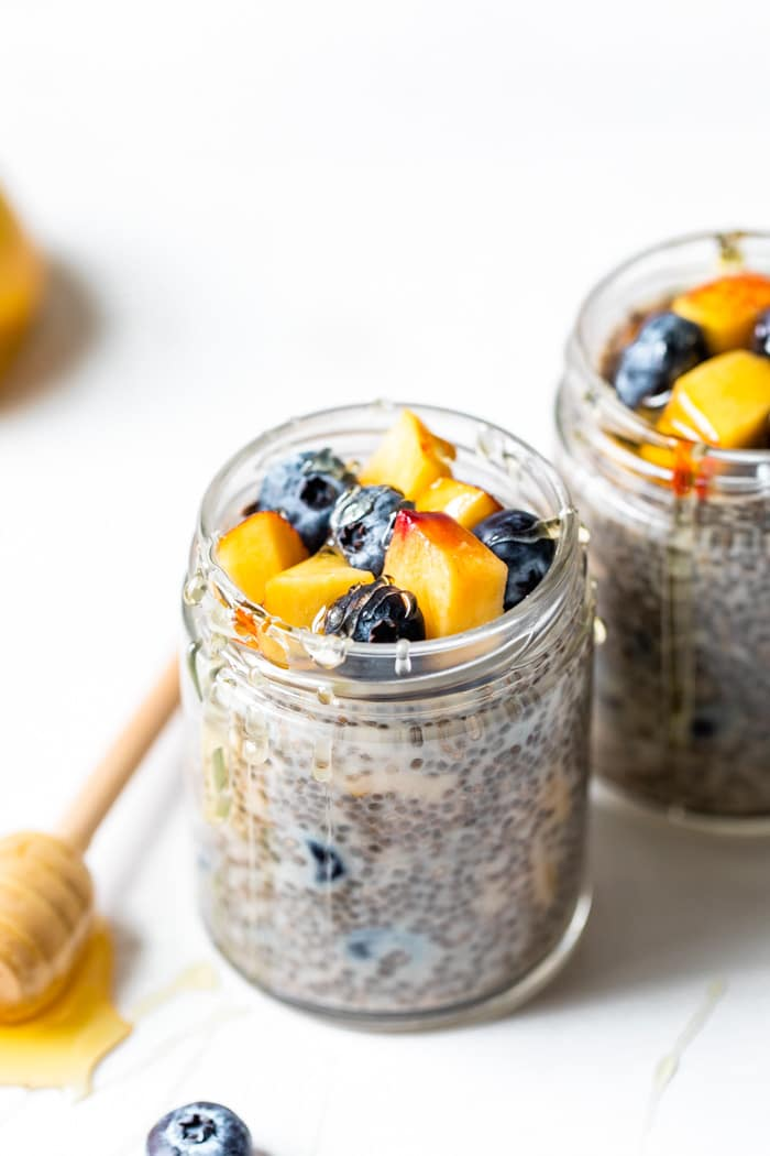 jar of chia seeds and milk topped with nectarine and fresh blueberries