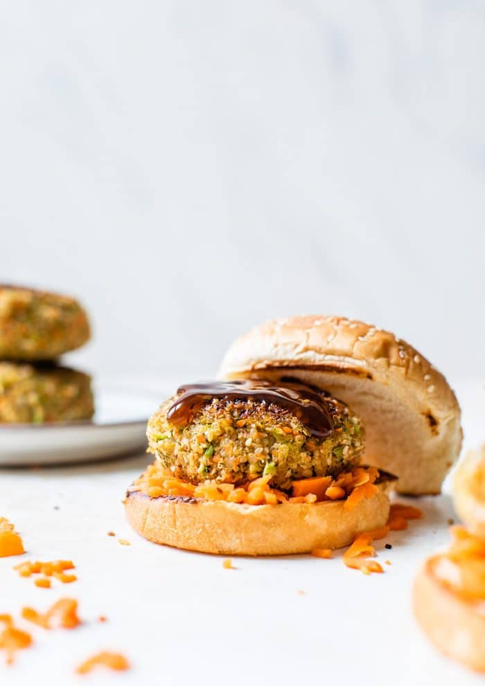 burger on a bun with shredded carrots around