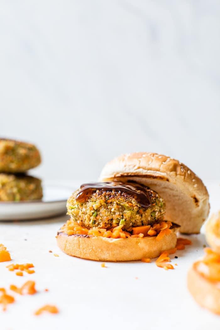 burger on a bun with shredded carrots around
