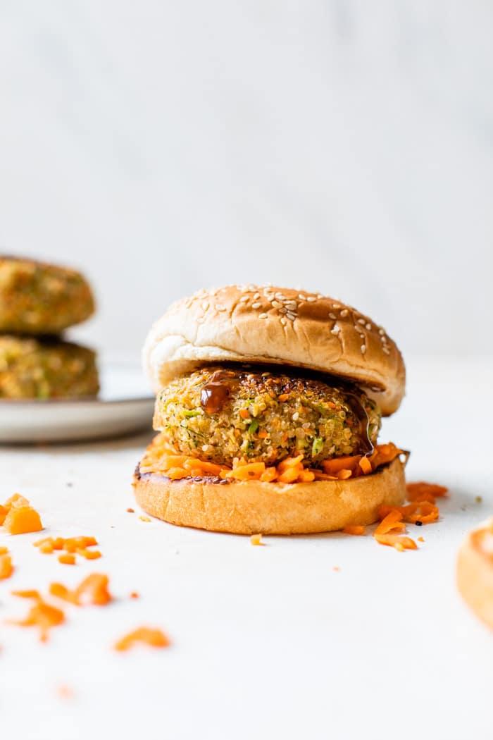 burger on a bun with shredded carrots around it