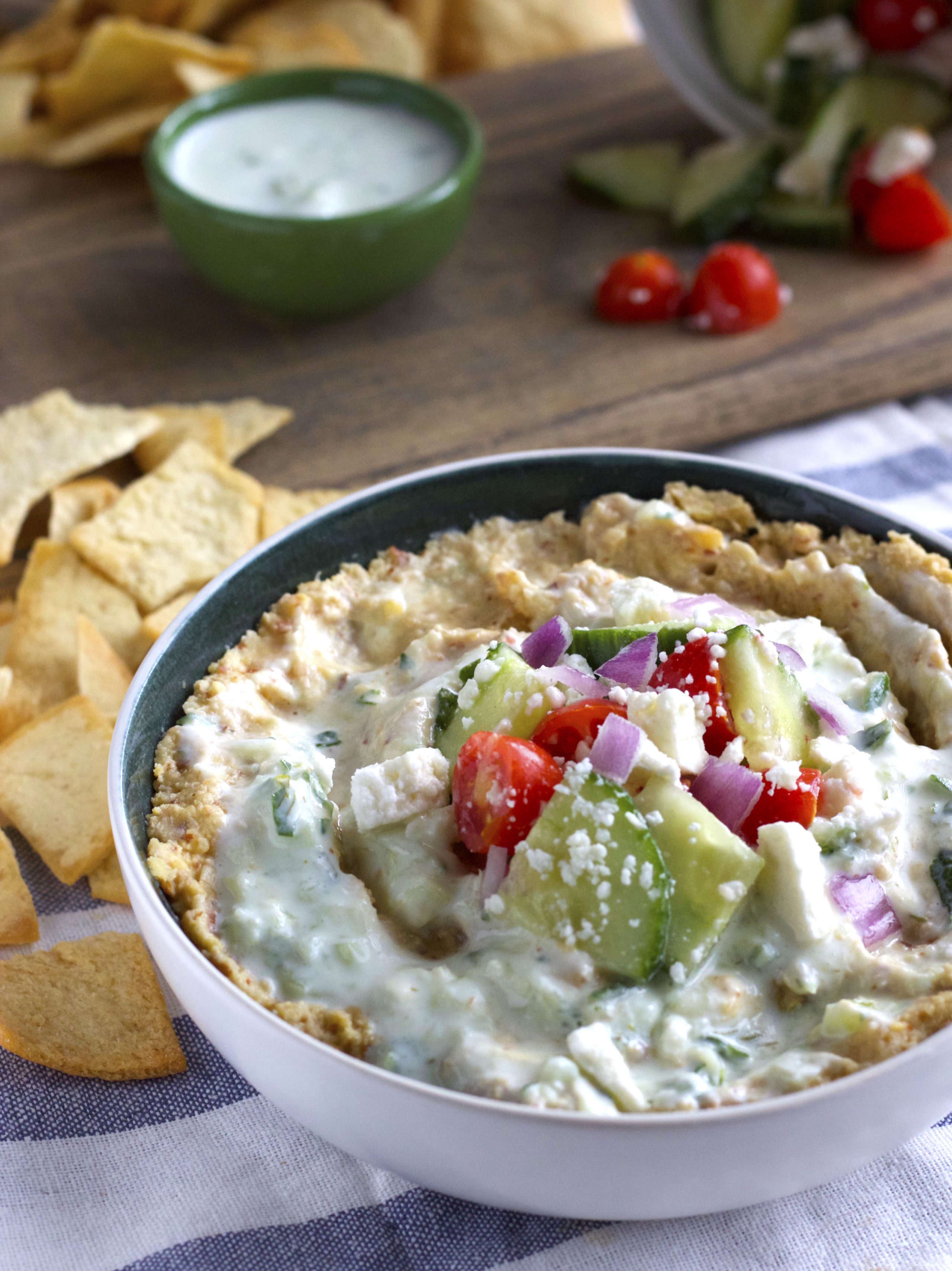 Creamy hummus made from almonds and topped with tzatziki sauce made from yogurt. A healthy party appetizer! | thealmondeater.com