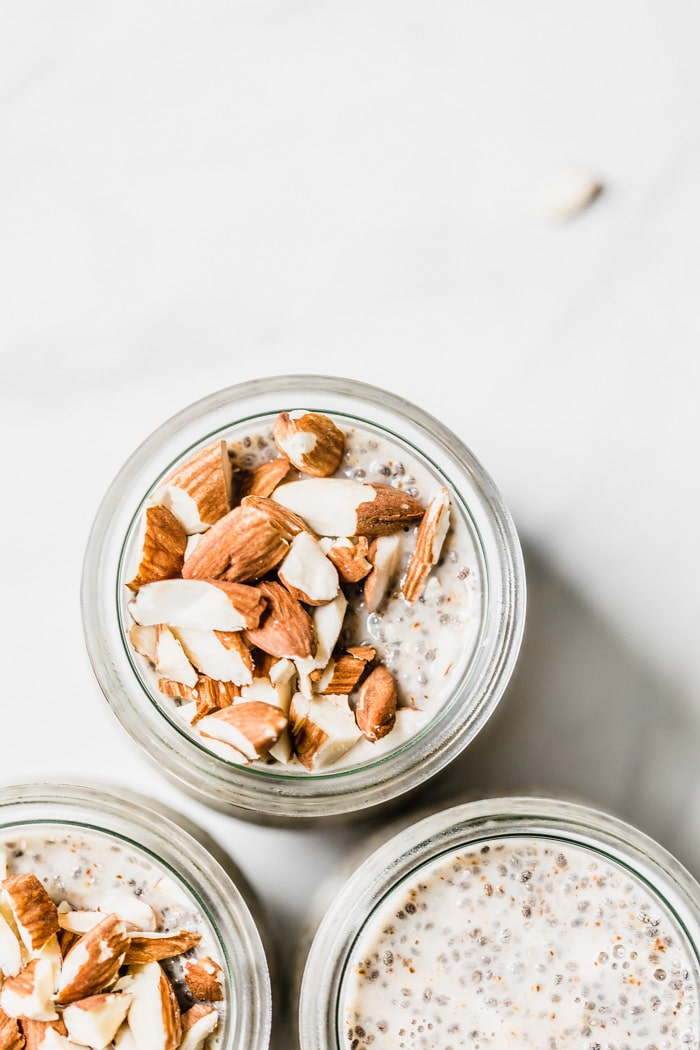Three jars of chia pudding shot overhead, two of them are topped with crushed almonds