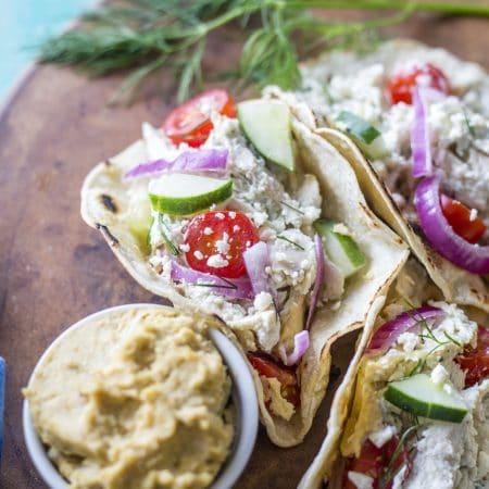 Mediterranean Chicken Tacos filled with tzatziki sauce, chicken, hummus, and veggies!