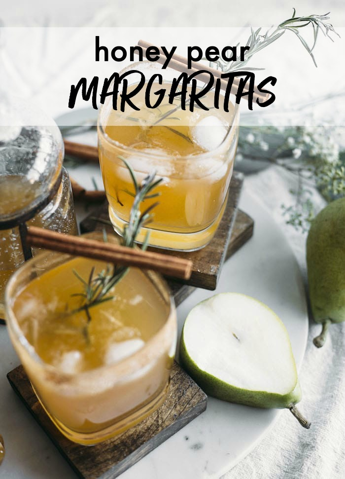 A pear margarita with a rosemary sprig and cinnamon sticks as a garnish
