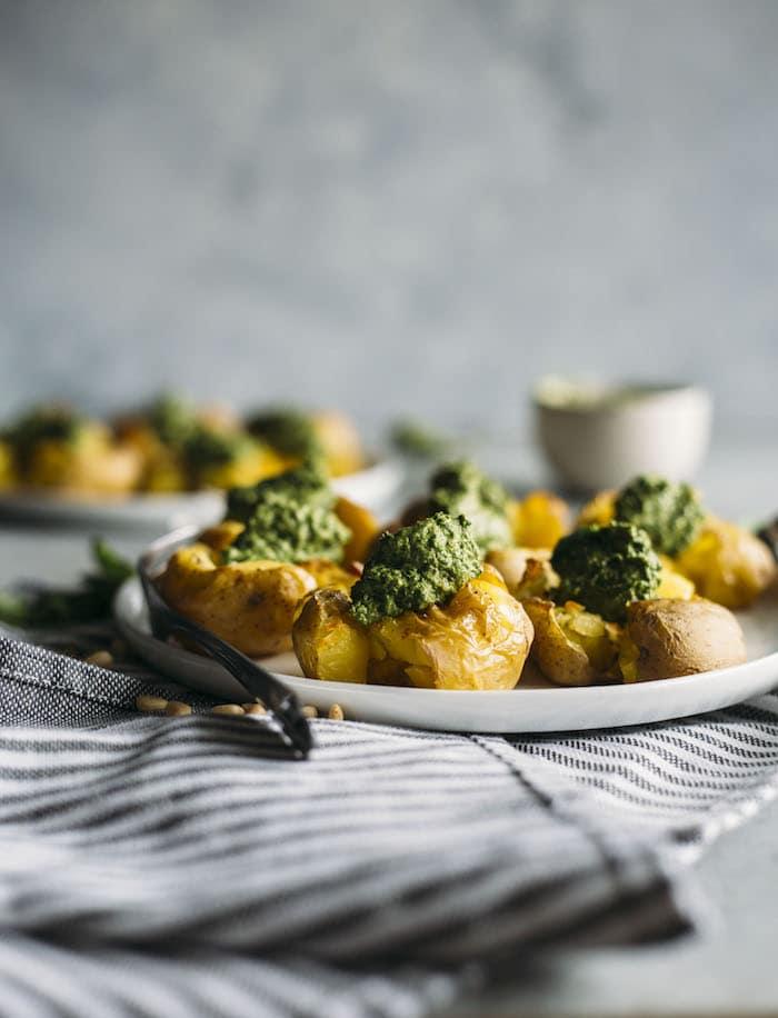 Pesto Smashed Potatoes | Crispy smashed potatoes topped with a vegan-friendly kale pesto!