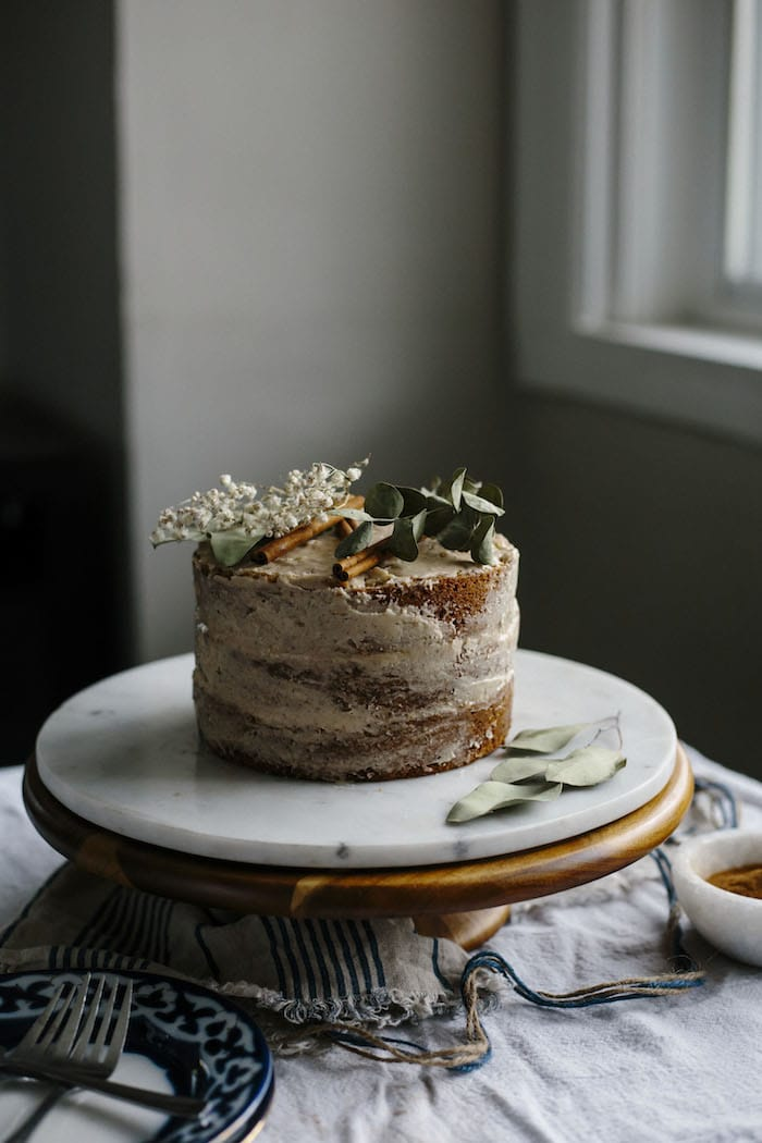 A three layer vanilla cake on a cake stand topped with chai icing