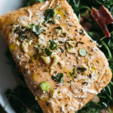 Whole30 Garlic Salmon | Salmon marinaded in garlic atop a bacon and watercress salad that's Whole30-approved | thealmondeater.com