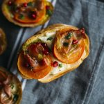 Prosciutto Persimmon Bruschetta | Bread topped with burrata cheese, persimmons, prosciutto AND pomegranate seeds | thealmondeater.com