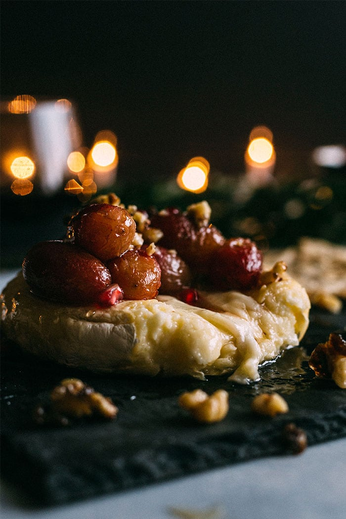 Baked brie topped with roasted grapes, caramelized walnuts and honey, aka the perfect party appetizer! | thealmondeater.com
