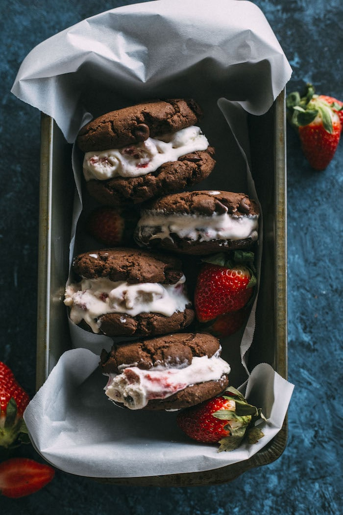 No Churn Strawberry Ice Cream smashed between two double chocolate chip cookies! | thealmondeater.com