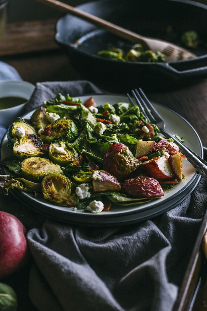 Brussels Sprouts Salad topped with roasted red potatoes, goat cheese and an easy leek dressing | thealmondeater.com