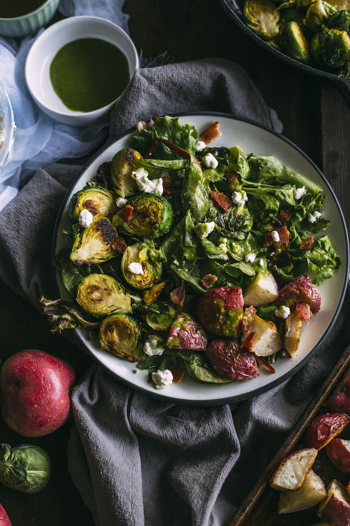 Brussels Sprouts Salad topped with roasted red potatoes, goat cheese and leek dressing | thealmondeater.com