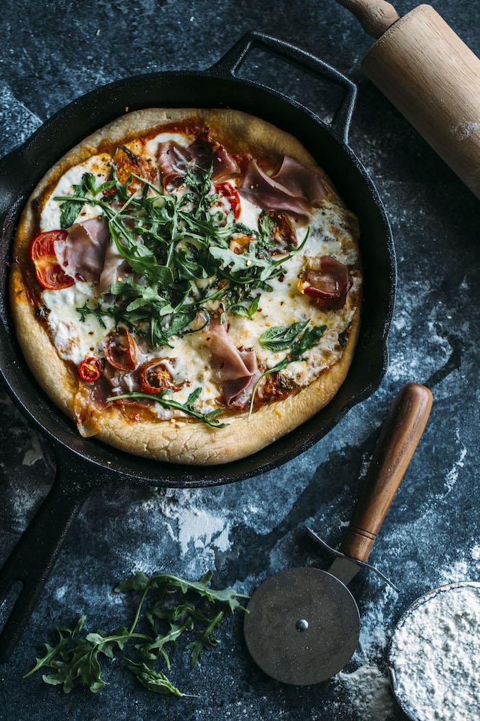 A delicious skillet pizza topped with fresh mozzarella, prosciutto and arugula   thealmondeater.com