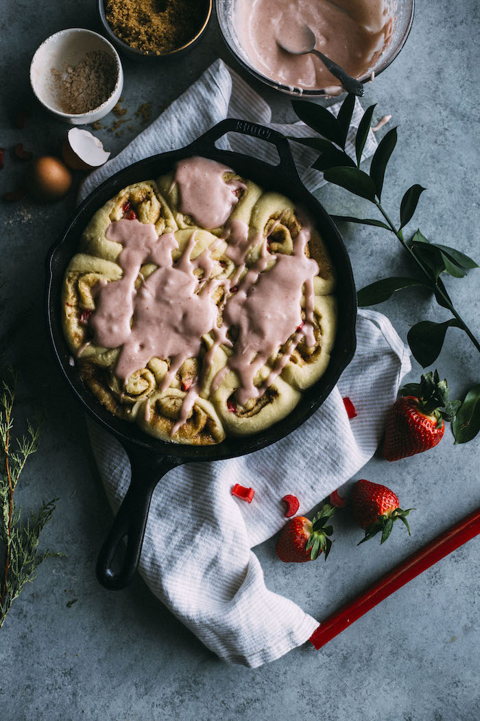 Strawberry rhubarb cinnamon rolls filled with fresh strawberries and rhubarb and topped with a fresh glaze! | thealmondeater.com
