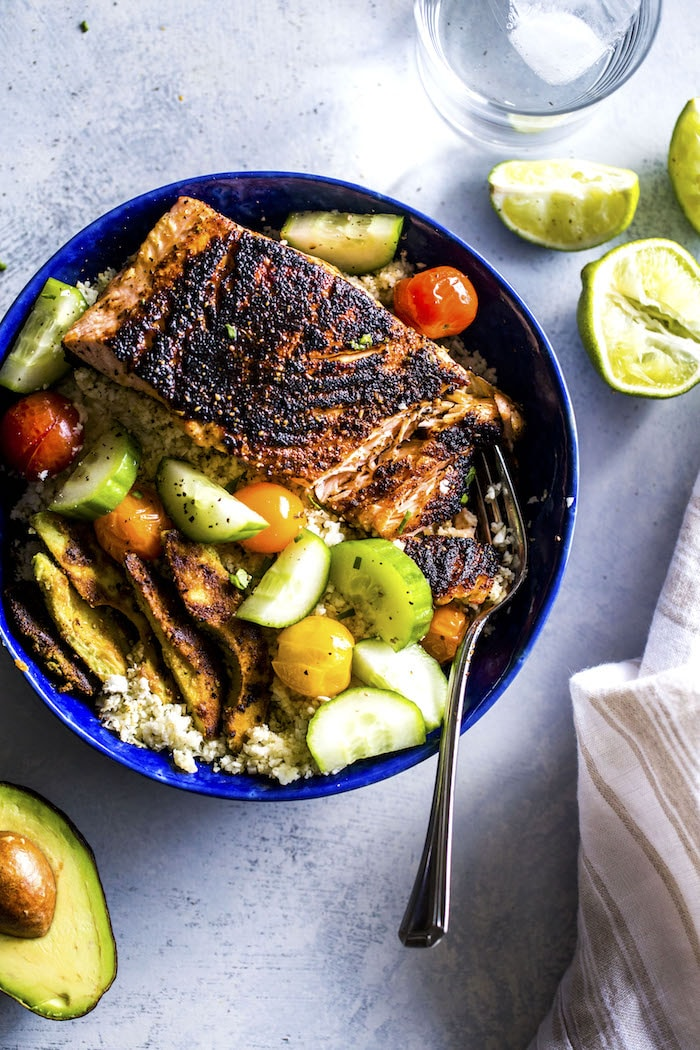 "A Whole30 salmon bowl made with cauliflower rice, blackened salmon and ""breaded"" avocado!"