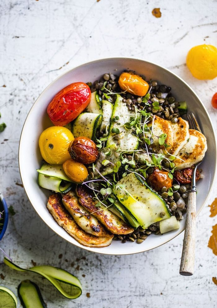A fresh lentil salad topped with fried halloumi, roasted tomatoes and zucchini   thealmondeater.com