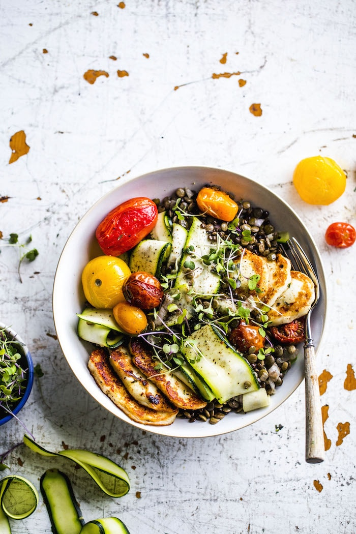 A fresh lentil salad topped with fried halloumi, roasted tomatoes and zucchini! | thealmondeater.com
