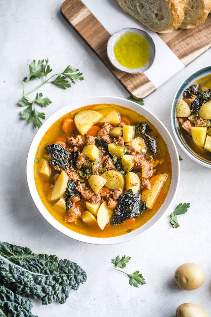 bowl of soup with potatoes, kale and sausage