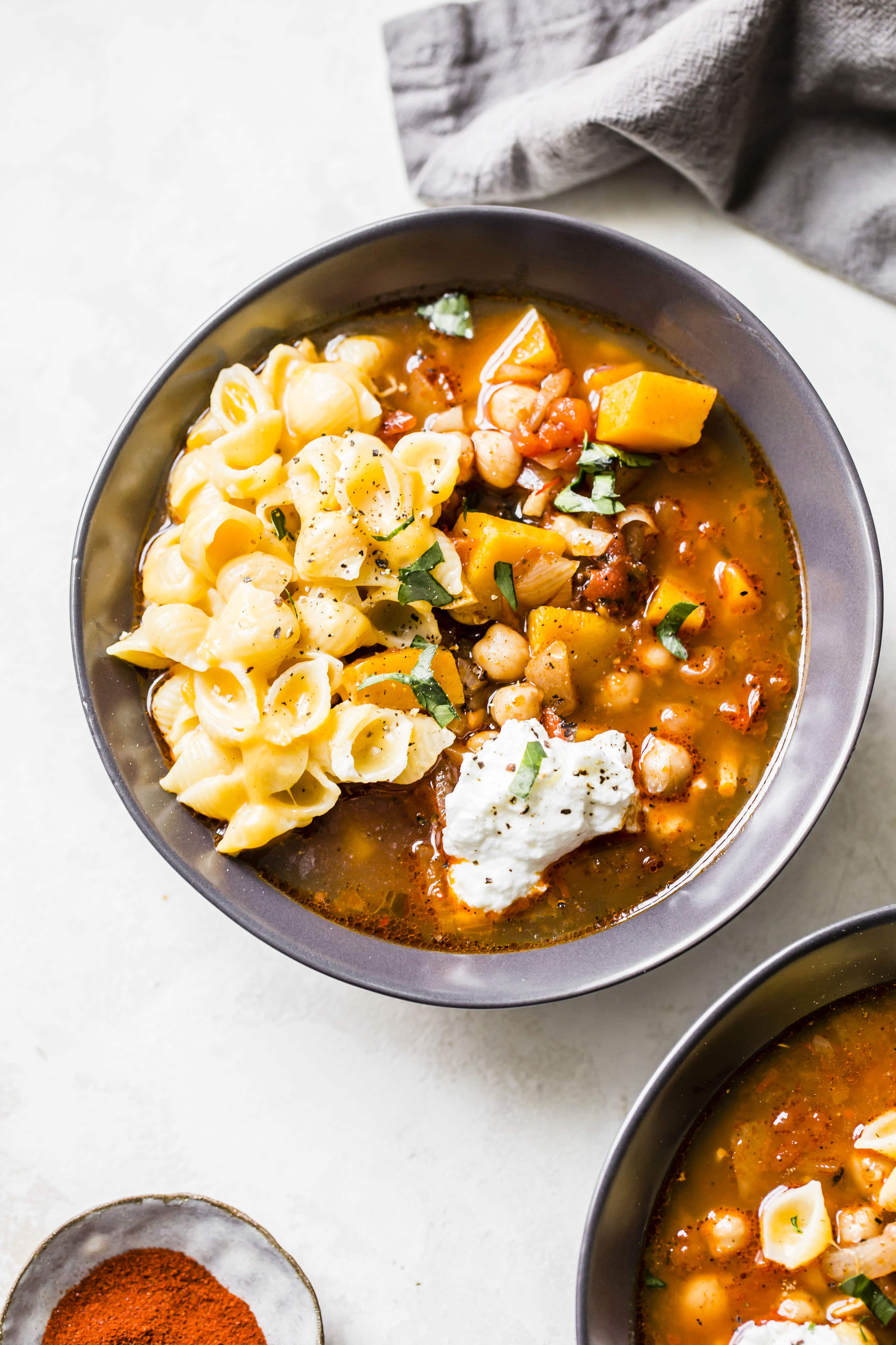 A bowl of butternut squash chickpea chili topped with mac and cheese and yogurt.