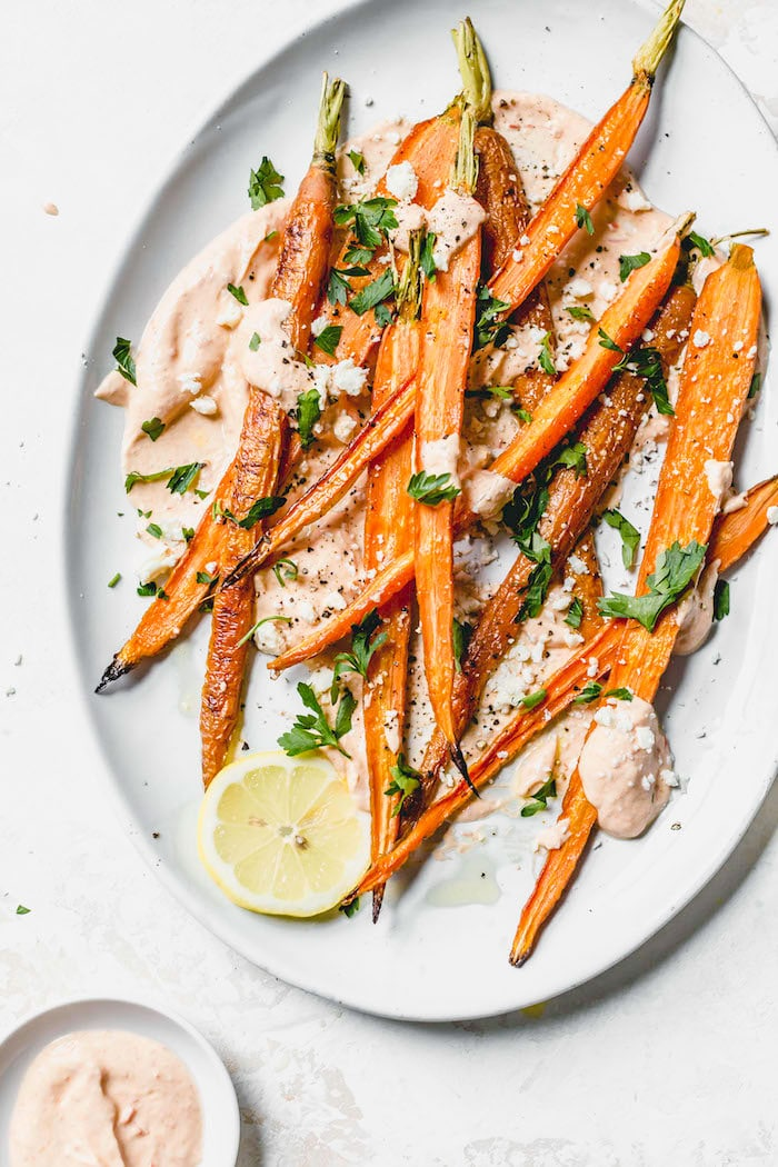 A plate of roasted carrots over yogurt and topped with fresh herbs.