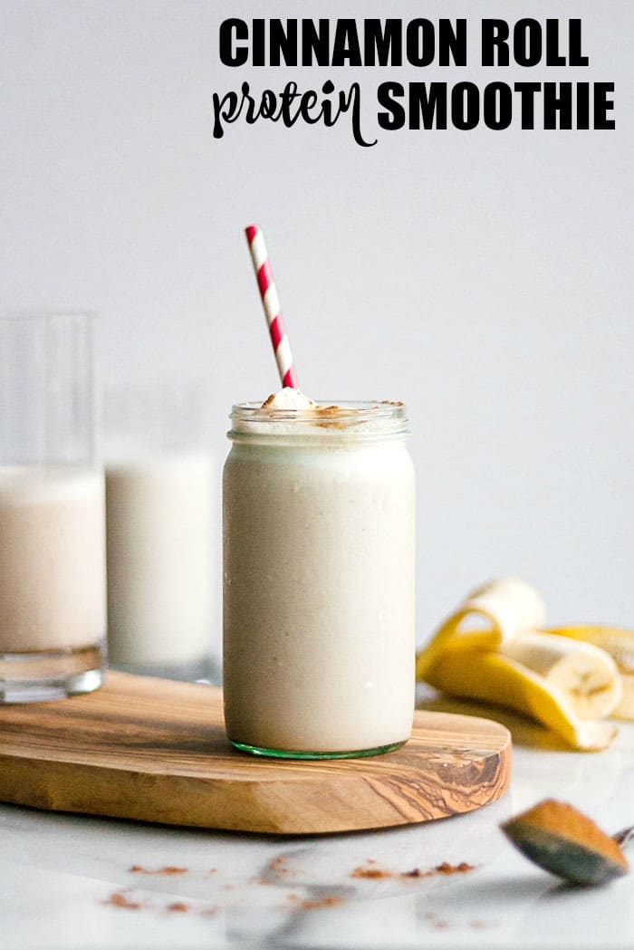 Cinnamon smoothie in a tall glass with a straw sitting on a cutting board