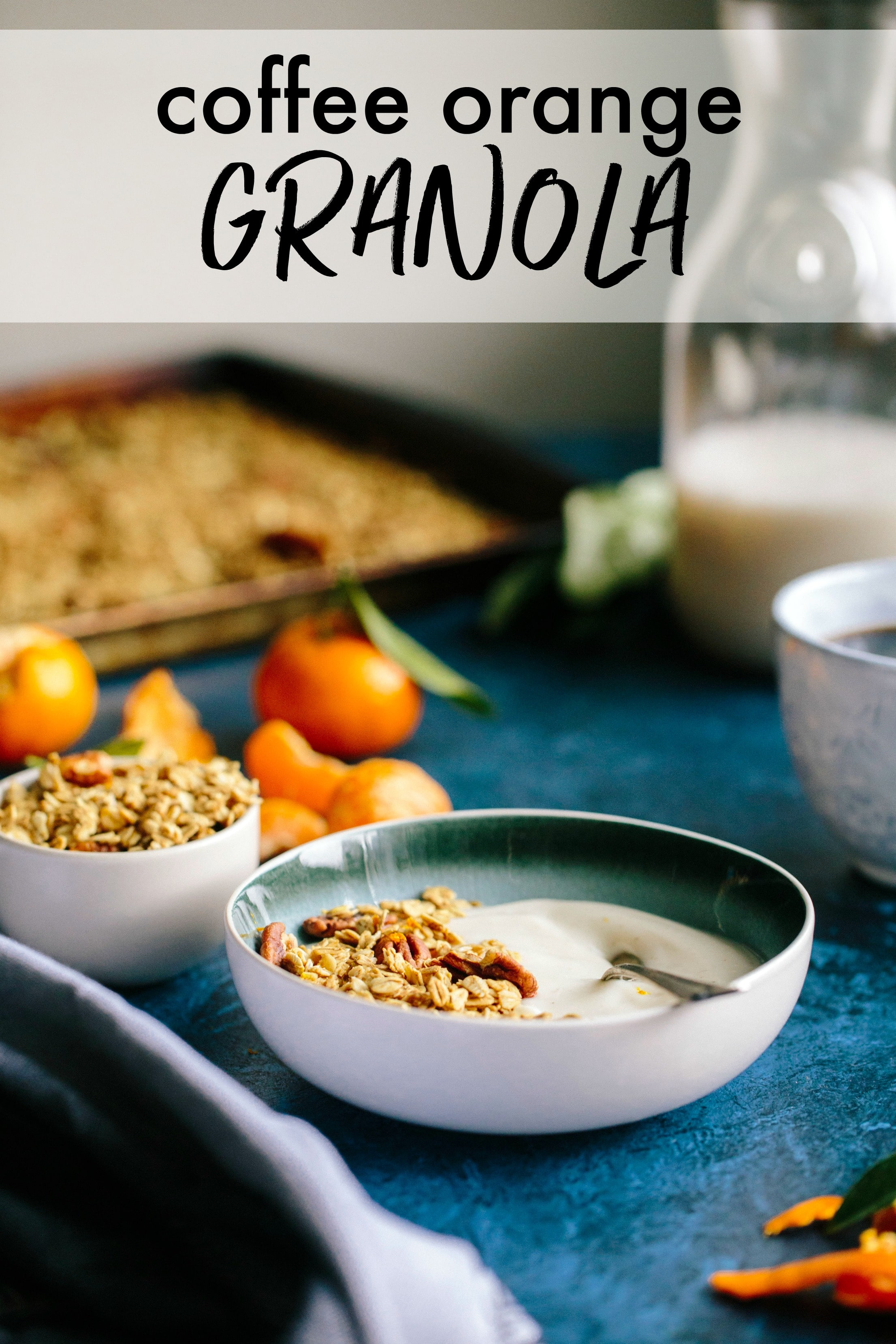 A bowl of granola with a baking sheet of granola behind it and a jar of milk.