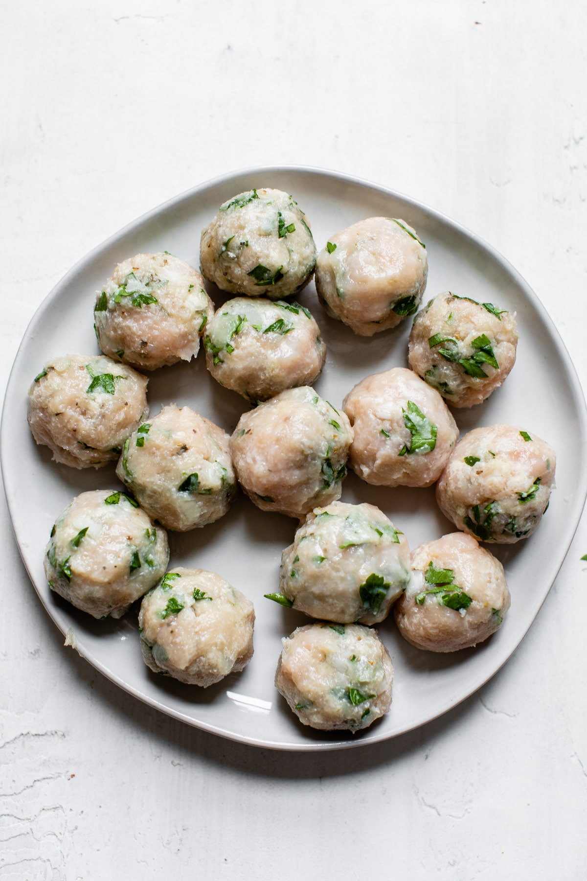 uncooked meatballs on a plate
