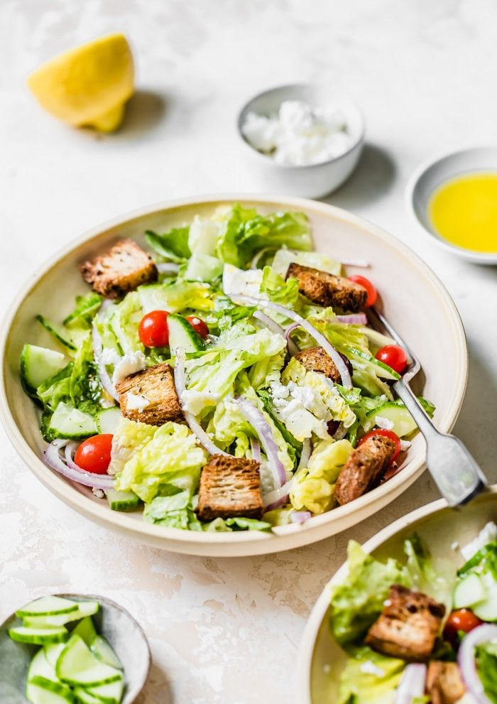 A salad filled with tomatoes onion and croutons on a table with olive oil, feta cheese and cucumbers.