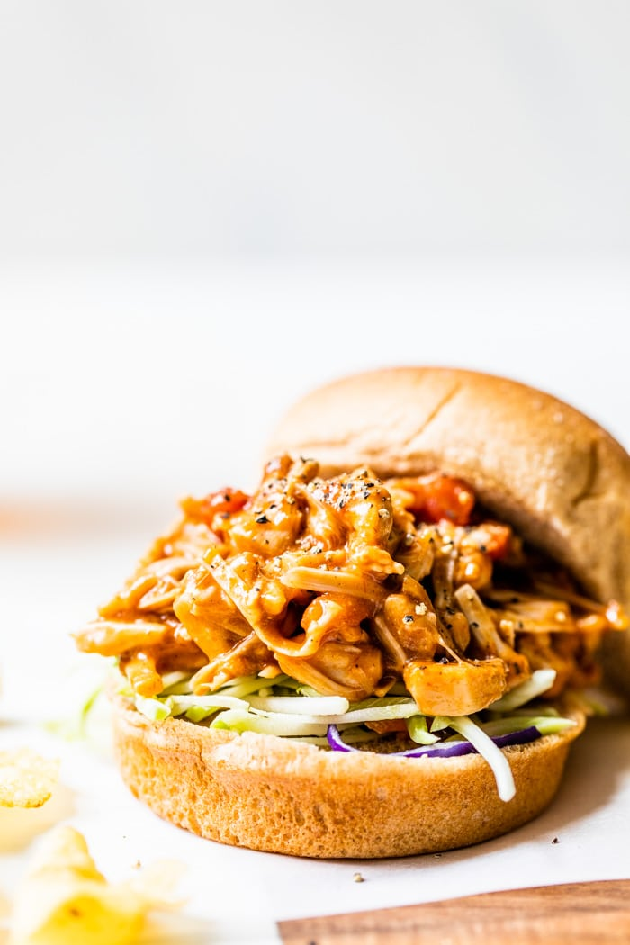 A hamburger bun filled with barbecue pulled jackfruit
