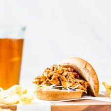 A hamburger bun filled with pulled jackfruit served with chips and beer