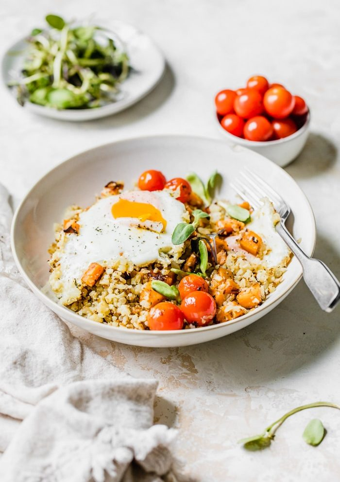 A bowl of cauliflower rice topped with tomatoes, sweet potato and a fried egg