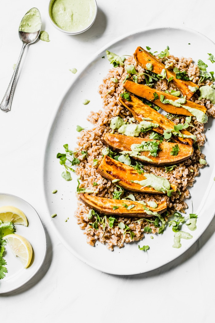 Sweet potato wedges on top of farro drizzled with tahini sauce