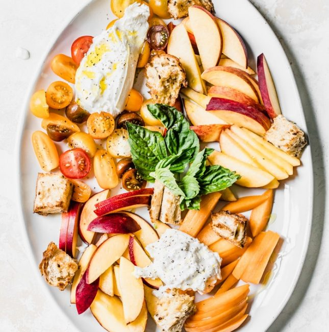 Salad made with stone fruit, bread, burrata cheese and fresh basil