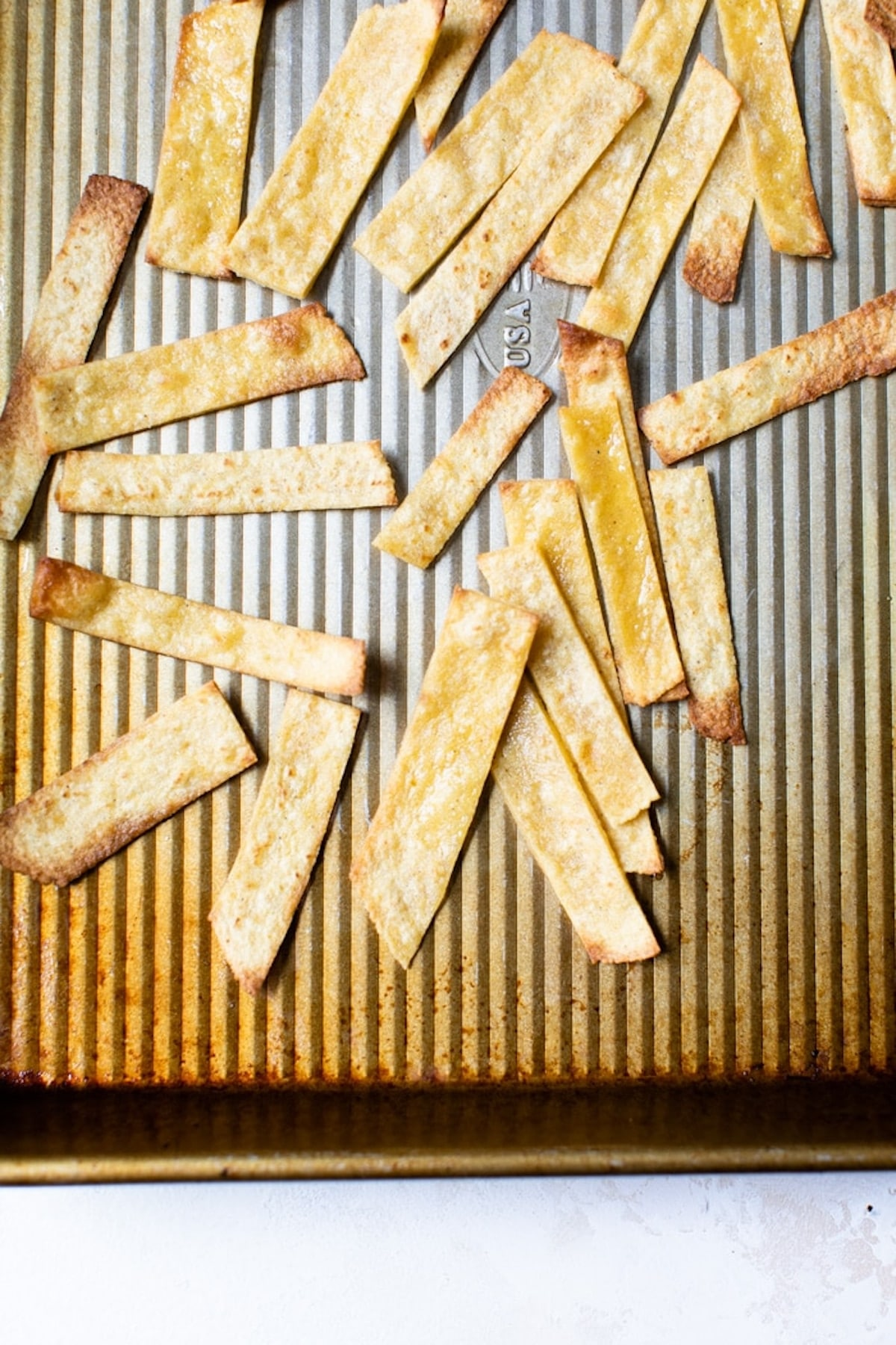 tortilla strips on a baking sheet