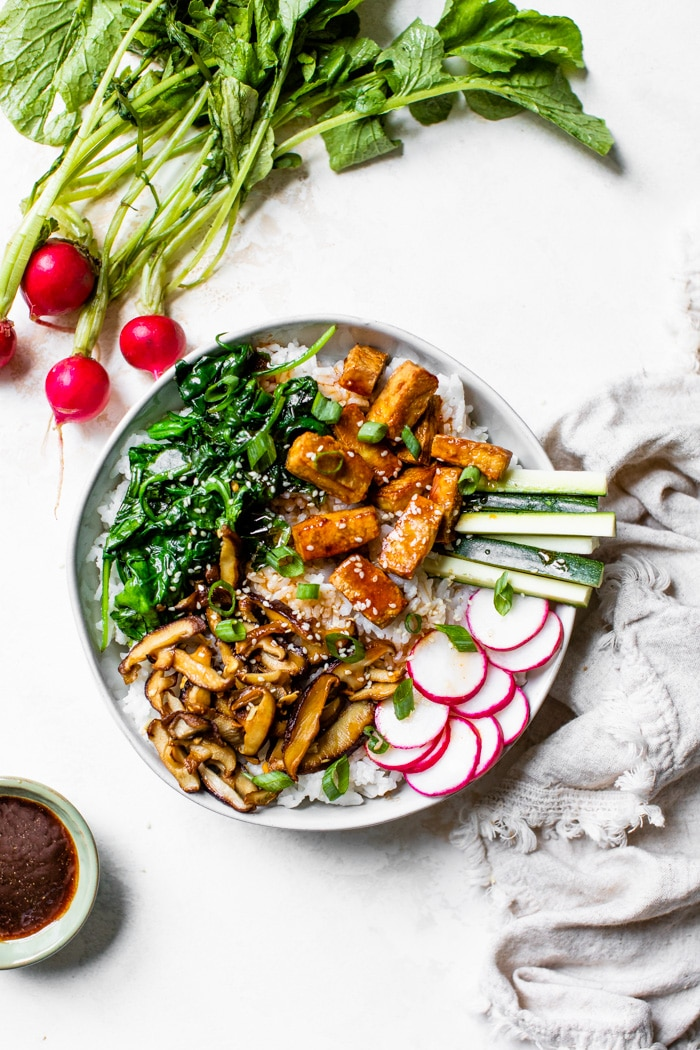a bowl of bibimbap made with tofu, mushrooms and spinach