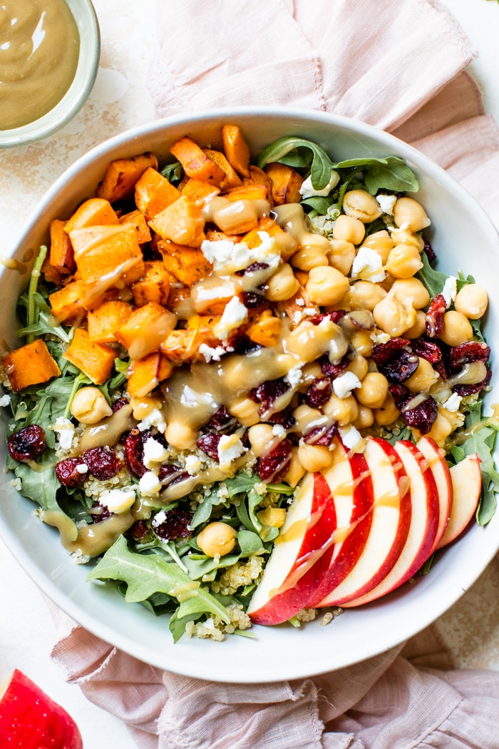 bowl filled with arugula, chickpeas, sweet potato, apples and goat cheese