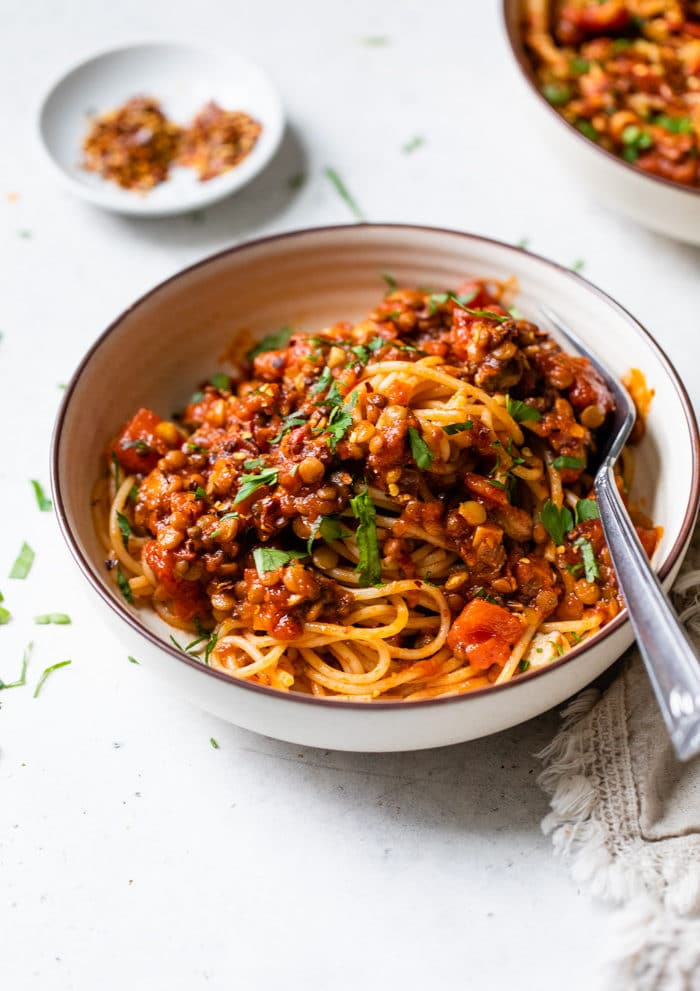 a bowl of pasta with lentils and red sauce