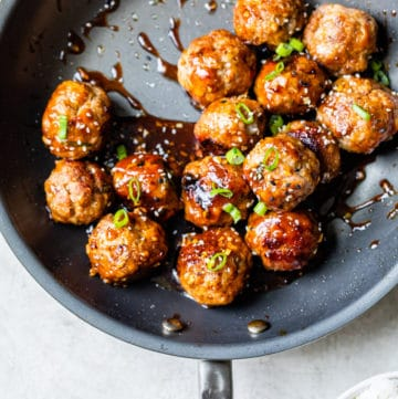 meatballs in a skillet with sauce over top