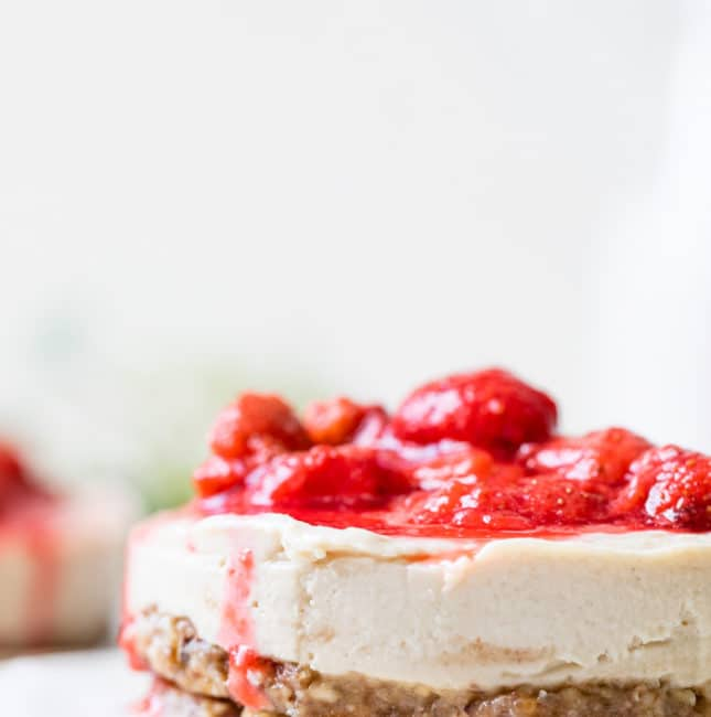 close up shot of frozen cheesecake topped with strawberries