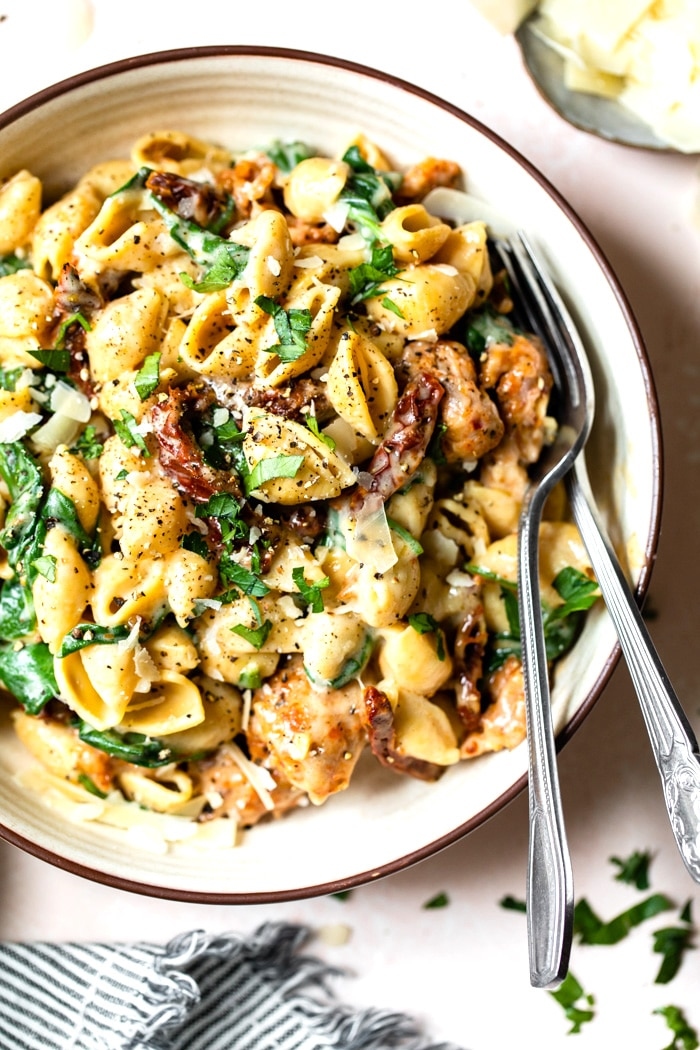 a bowl of pasta with sausage and spinach