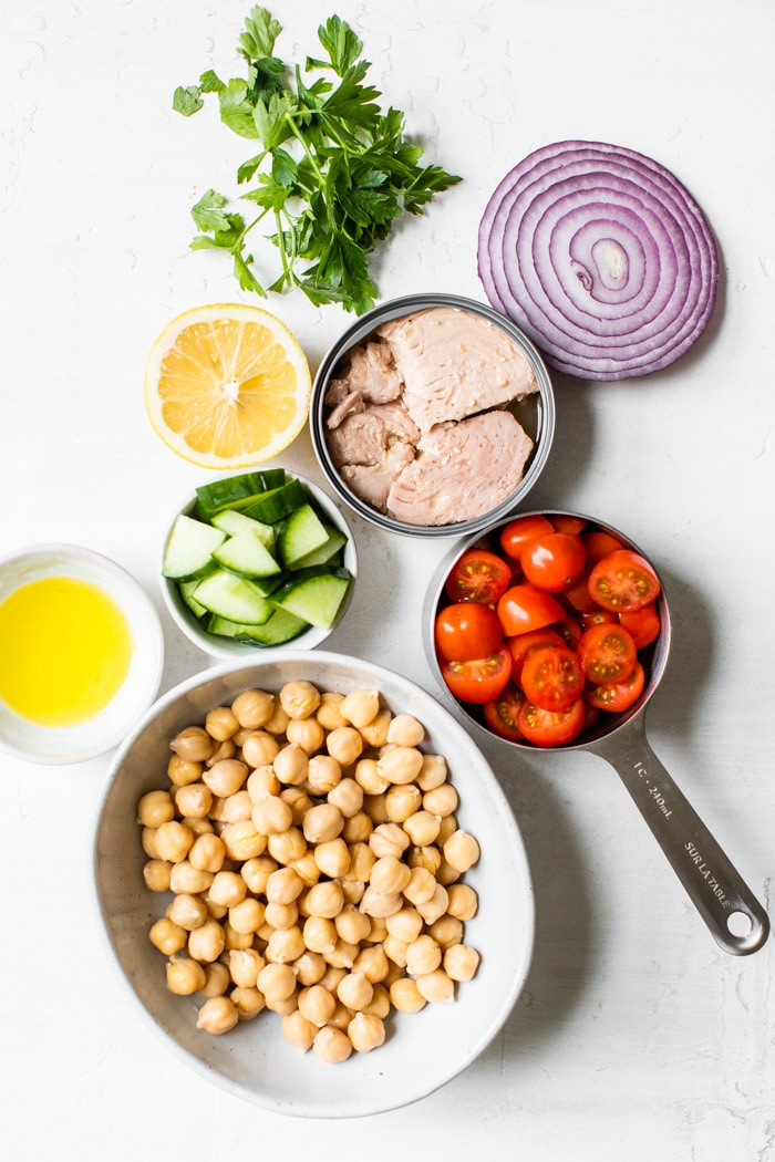 tuna, chickpeas, tomato, onion, cucumber, lemon, and parsley on a table