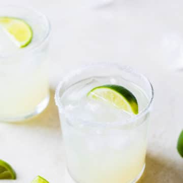 glass filled with ice lime juice and a lime wedge