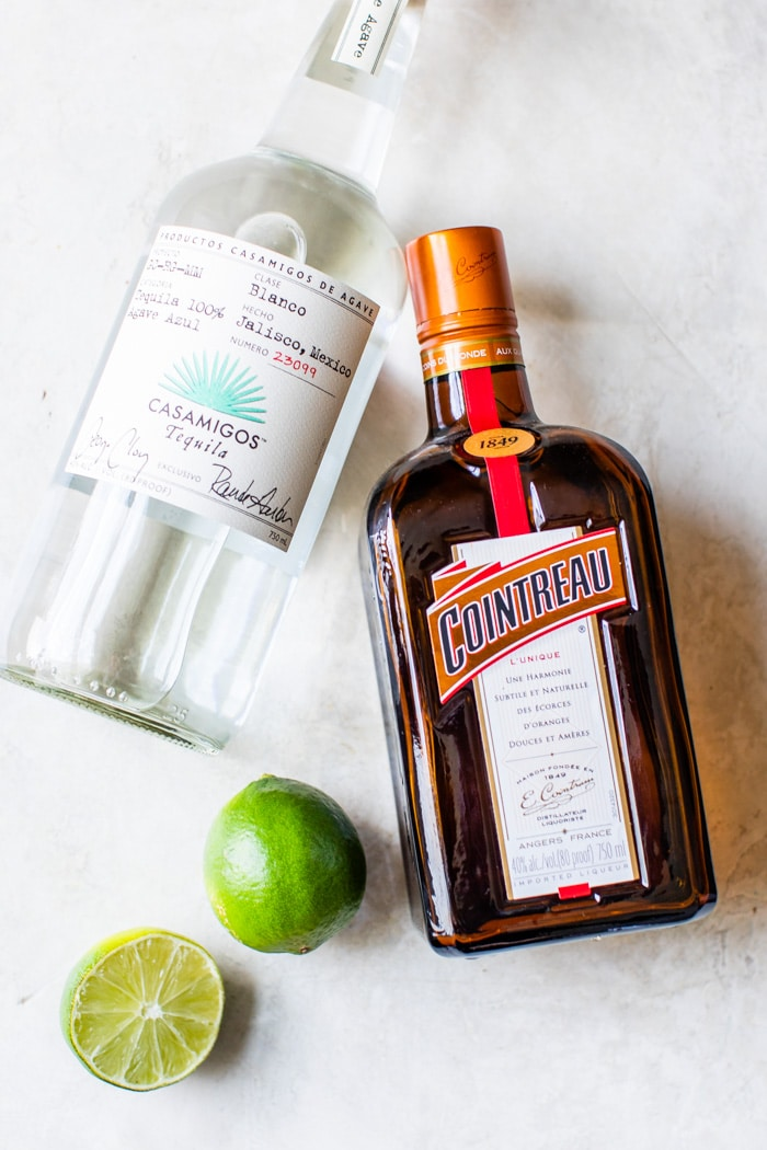 bottle of tequila, cointreau and two limes