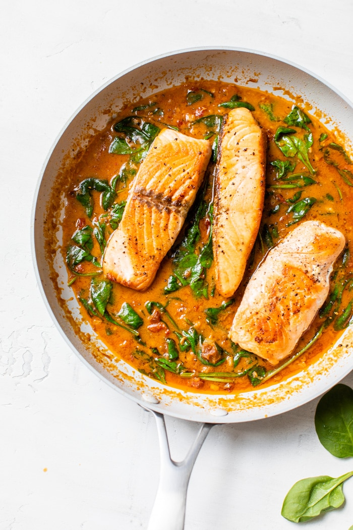 salmon in a skillet with sun-dried tomato sauce
