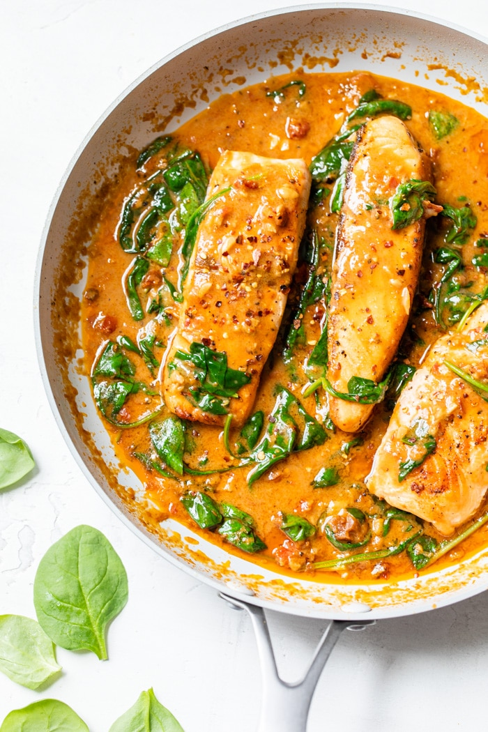 salmon in a skillet with tomato sauce and spinach