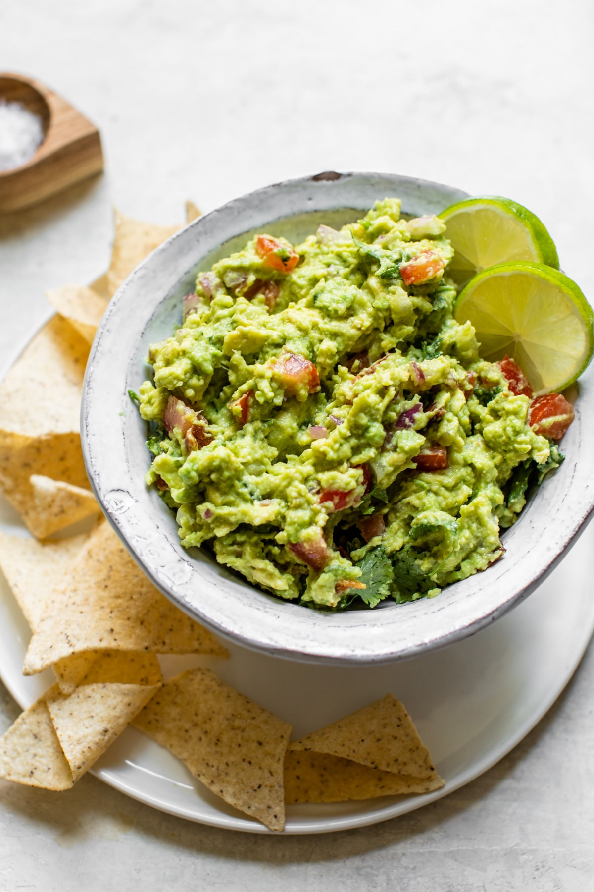 guacamole in a bowl with tortilla chips around it