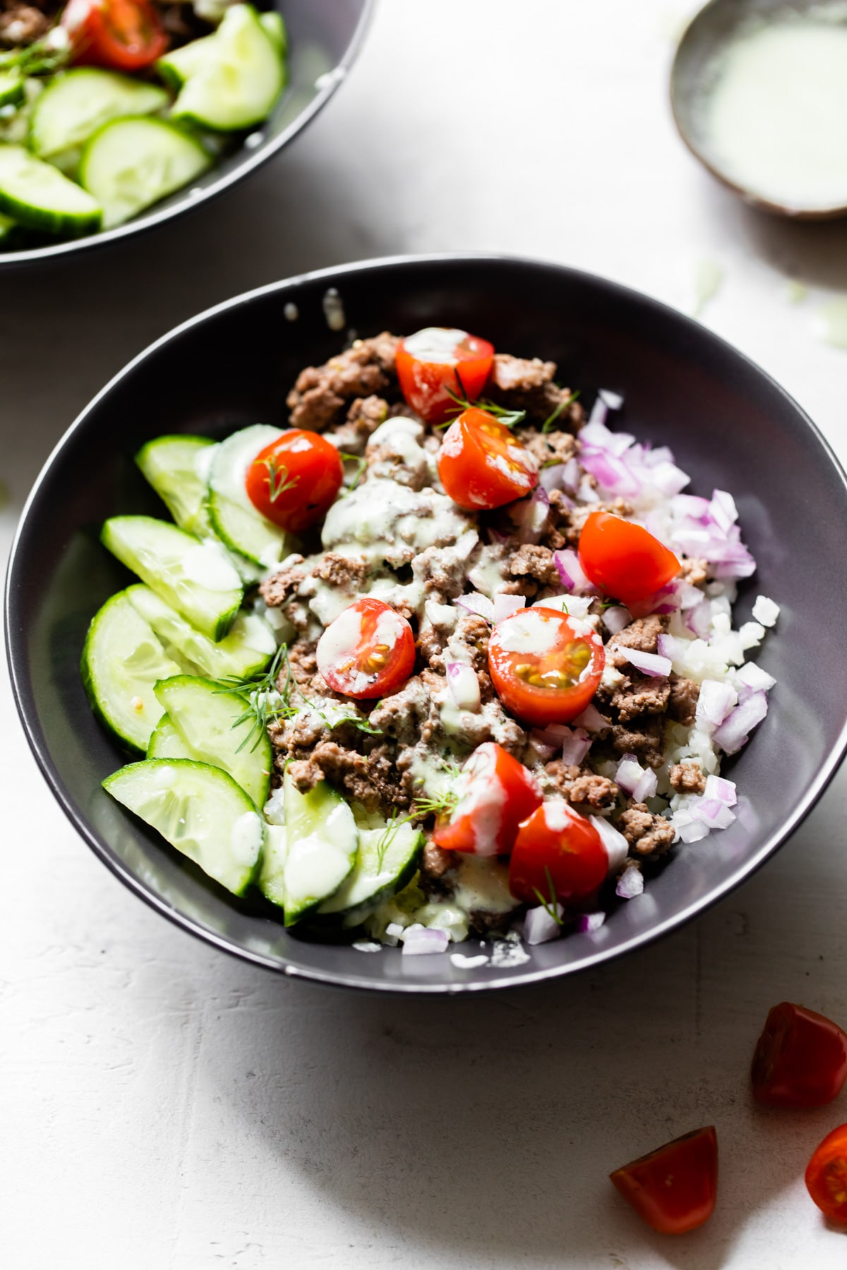bowl with lamb, cucumber, tomatoes, and red onion