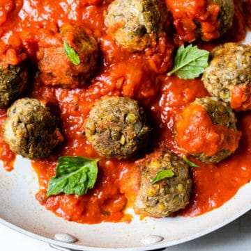 meatballs in a skillet topped with marinara sauce